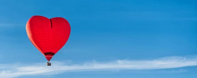 空に赤いハート型のエアバルーン、バナー、日光