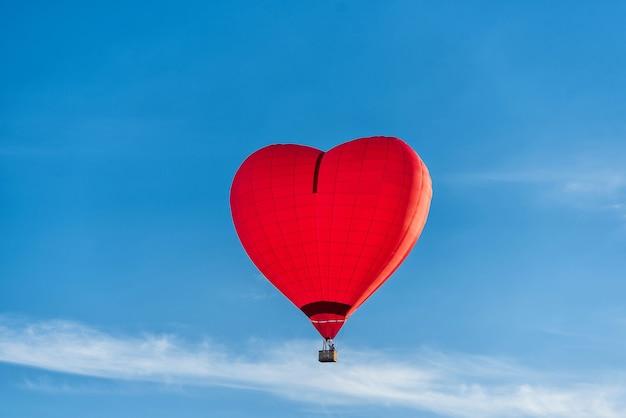 赤いハート型の気球が青い空を飛んでいます。はがきのコンセプト