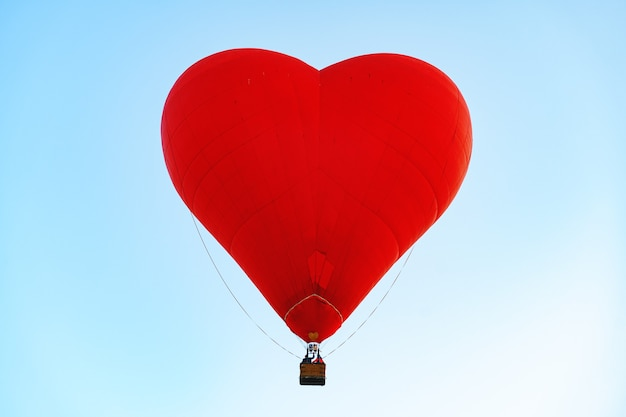 Red heart-shaped air balloon flying in the clear sky