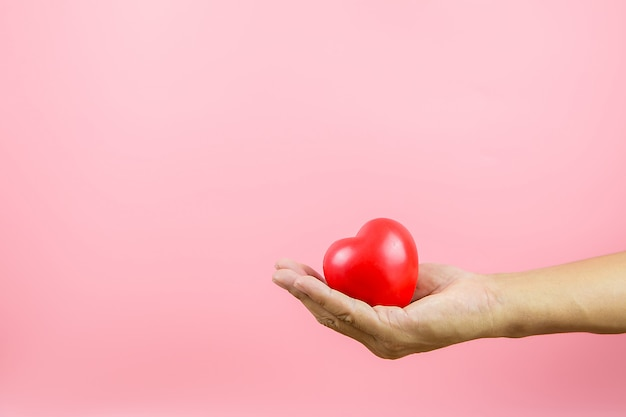A red heart shaped balloon in his hand against a pink background.