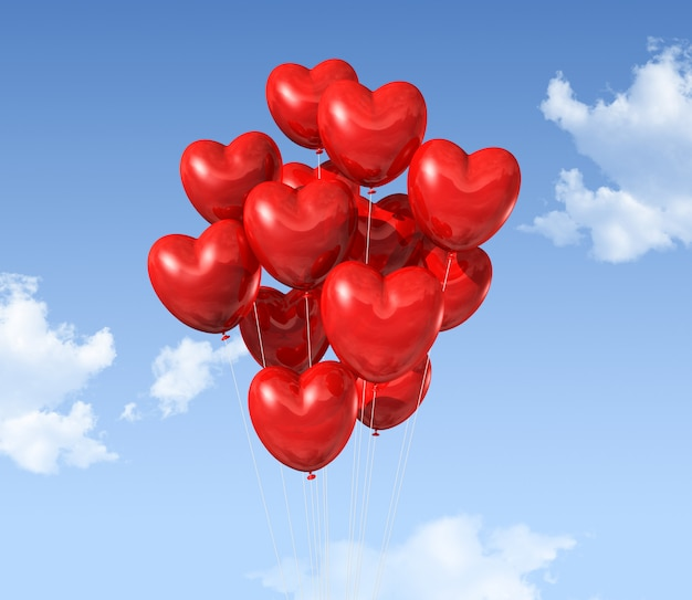 Red heart shaped balloons floating in the sky