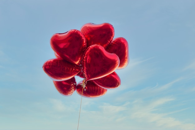 Red heart-shaped balloons with blue sky in vintage style, concept of love and valentine. love is in the air