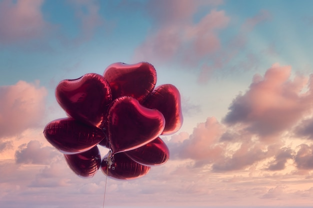 Red heart-shaped balloons with dramatic sky in vintage style, concept of love and valentine. love is in the air