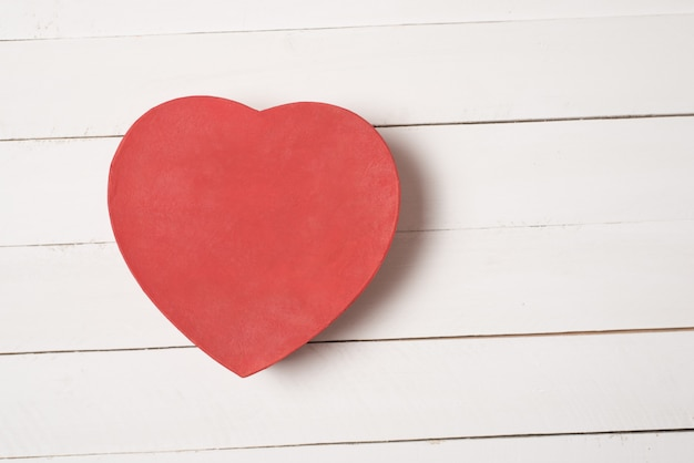 Red heart shaped box on white wooden table