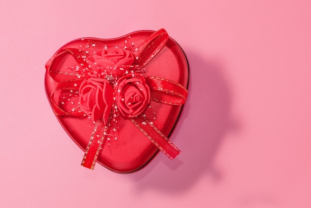 Red heart shaped box with made from steel with red ribbon close up.