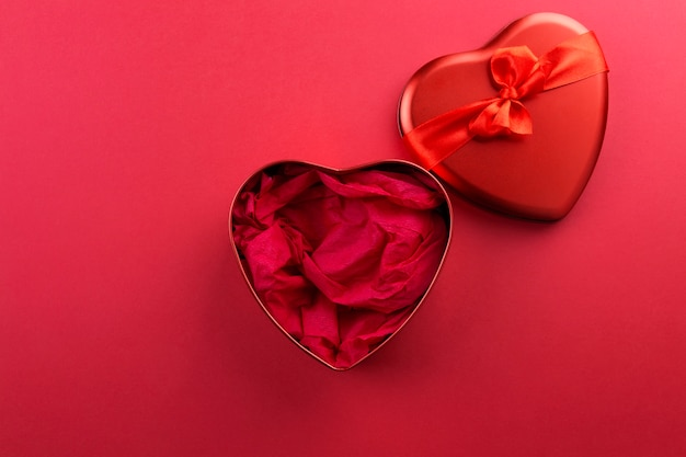 Red heart-shaped box with ribbon on red background