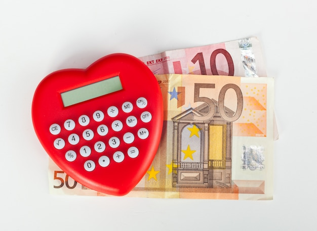 Red heart shaped calculator with euro banknotes.