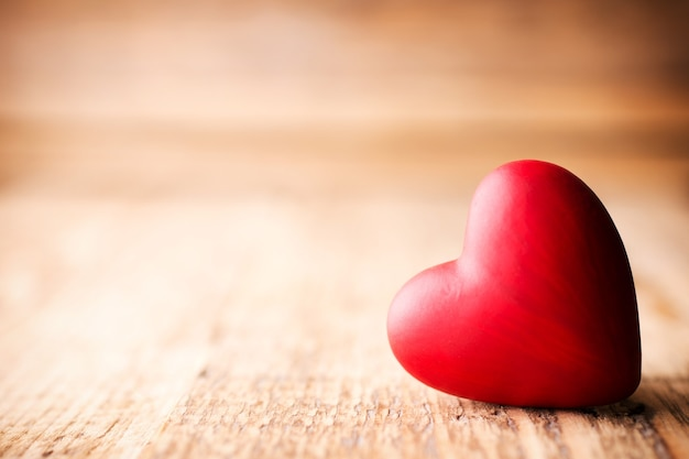 Красные конфеты в форме сердца на деревянном.