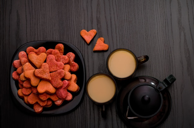 Red heart-shaped cookies, two cups of tea with milk and teapot. valentine's day, copyspace
