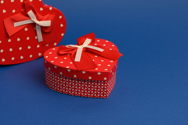 Red heart shaped gift box on blue wall, close up