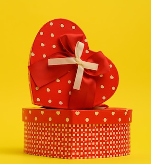 Red heart shaped gift box on a yellow wall, close up