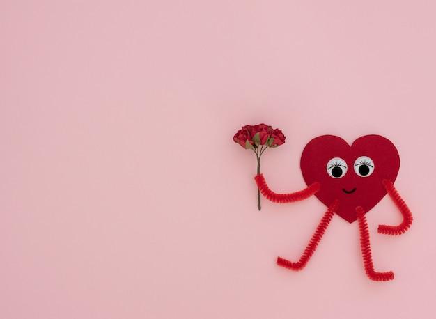 ピンクの背景にクラフト赤いバラの小さな花束を持つ赤いハート型のヒーロー。バレンタイングリーティングカード。バレンタインデー、愛、幸福、結婚式のコンセプト。コピースペースのあるフラットレイスタイル。