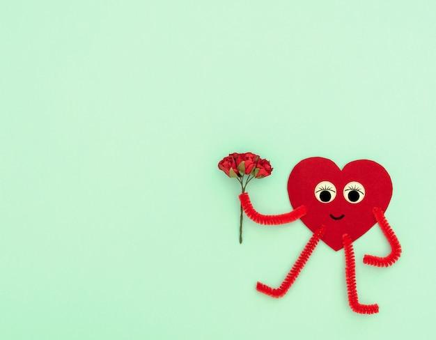 Красный герой в форме сердца с небольшим букетом красных роз на светло-зеленом фоне