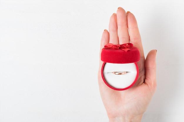 女性の手のひらにリングが付いた赤いハート型のジュエリーボックス、プレゼント、