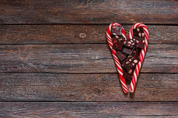 木の質感の表面に赤いハート型のロリポップとバレンタインデーのチョコレート