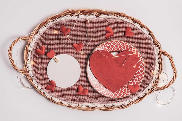 A red heart shaped object placed in a straw tray and a round white blank letterhead on a white background. declaration of love, valentines day, marriage proposals.