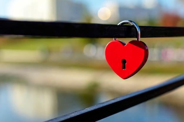 ぼやけた街の愛と忠誠の象徴のような赤いハート型の南京錠
