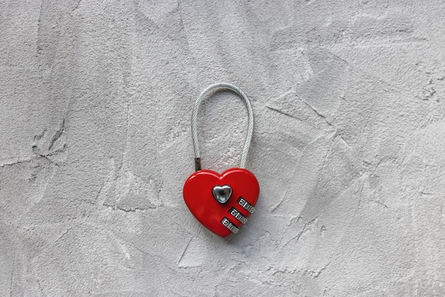 Замок в форме красного сердца или замок любви на сером фоне, замок для пары молодоженов на мост, забор, ворота. или безопасный кодовый замок для чемодана или велосипеда. копирование пространства крупным планом, концепция путешествий и любви