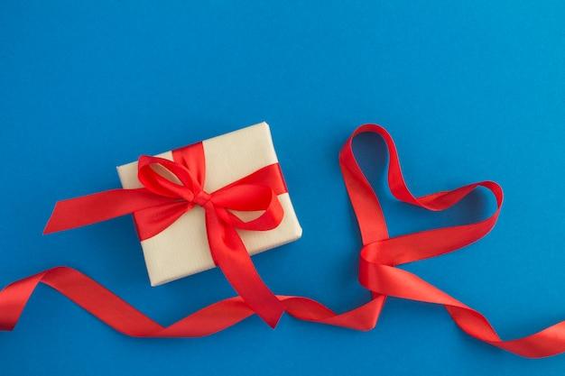 Красная лента в форме сердца и подарок на синей поверхности