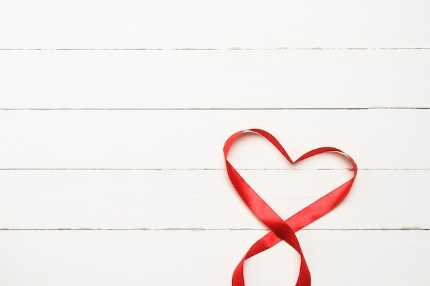 Red heart shaped ribbon over white wooden background