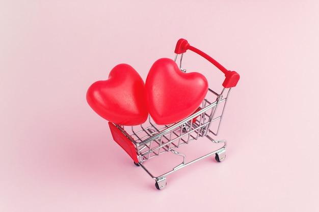 분홍색 배경, 쇼핑 및 사랑 개념에 미니 쇼핑 카트에 붉은 심장 모양.