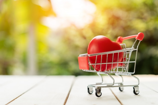 Red heart in the shopping cart on the wood. love shopping concept