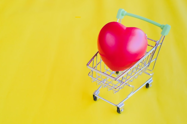 Red heart in shopping cart on yellow vintage background.