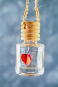 Red heart in a small glass jar on a gray concrete background. the concept of valentine's day.