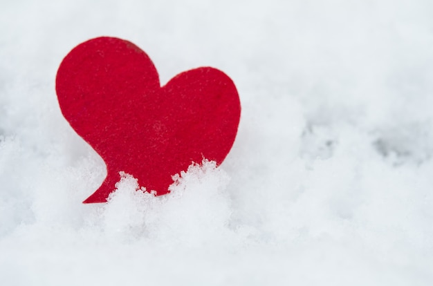 Red heart on snow