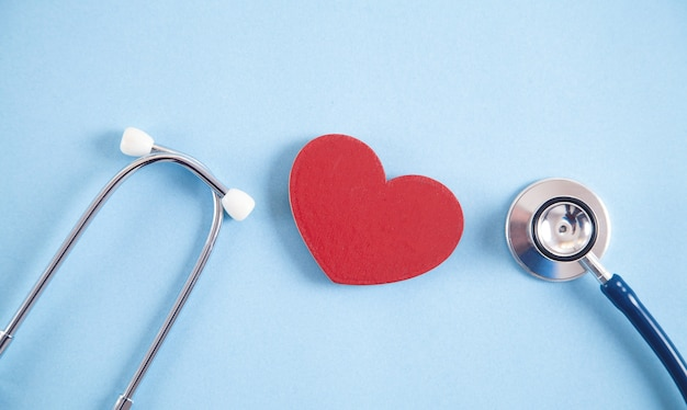 Red heart and stethoscope on the blue background.