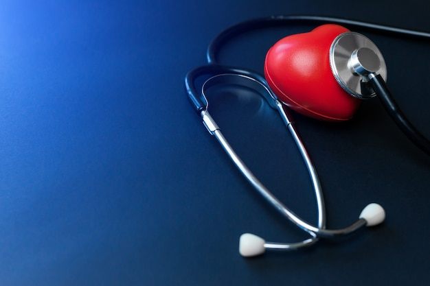 Red heart and stethoscope on blue paper. flat lay essential items for doctor using treat and care patient in hospital.