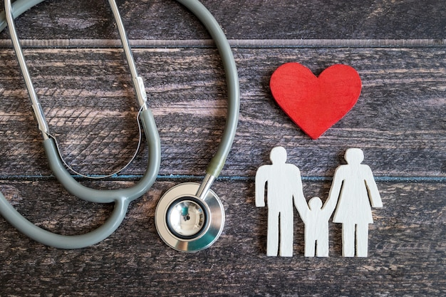 Red heart, stethoscope and icon family on wooden desk. medical insurance concept