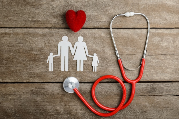 Red heart, stethoscope and paper chain family on wooden table