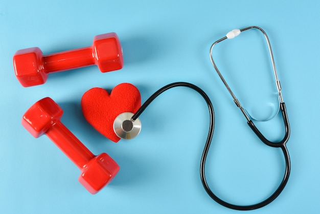 Red heart, stethoscope and red dumbbells. world health day, healthcare and medical concept, health insurance concept.