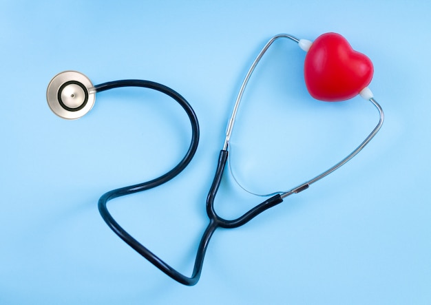 Red heart and stethoscope top view on blue background. listening heartbeat concept