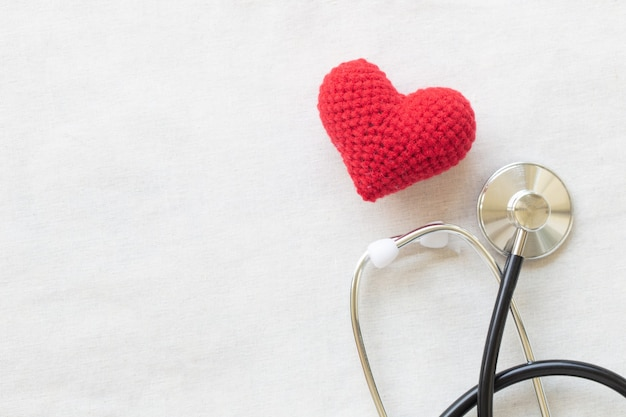 Red heart and stethoscope on white isolated background, copy space.