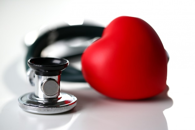 Red heart and a stethoscope on a white