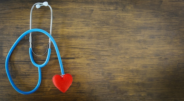 Red heart on stethoscope on wooden background