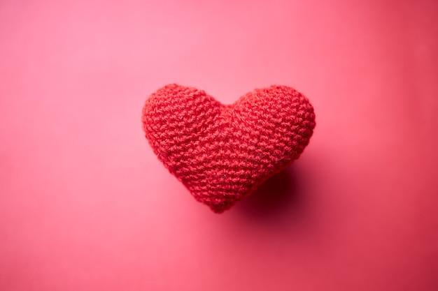 赤の上に赤いハートのシンボル。宇宙空間。ロマンスと愛の概念。シンプルさ