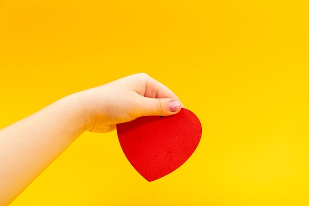 Red heart in teenager hand on yellow. valentine day concept.