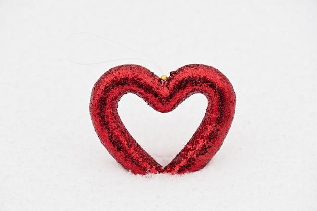 Красное сердце игрушка на фоне снега