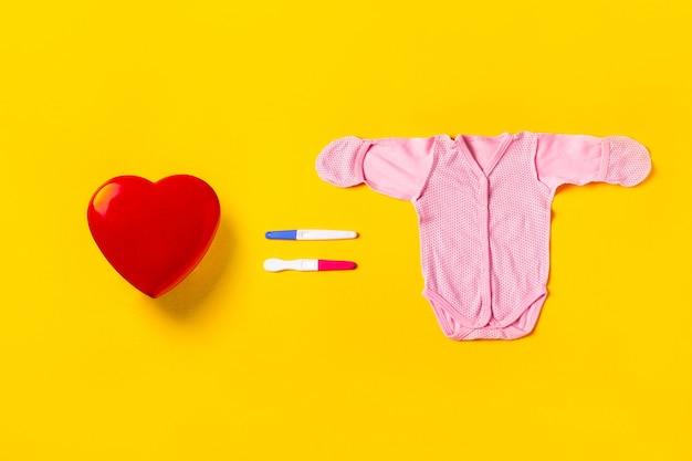 Красное сердце, два теста на беременность в форме равного и детский костюм