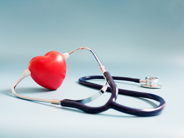 Red heart using deep blue stethoscope on the blue background