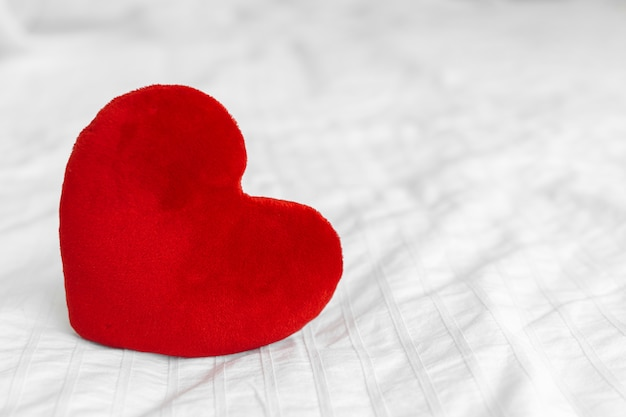 Red heart on white bed