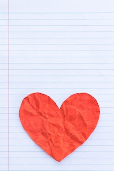 Red heart on white lined sheet of notepad