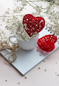 Red heart and white porcelain cup with a bouquet of small white flowers on a light background