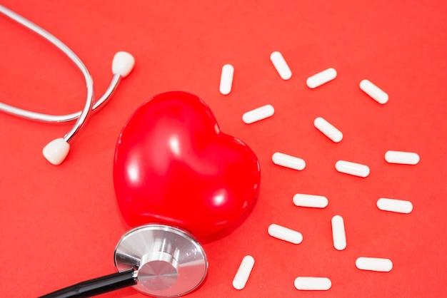 Красное сердце со стетоскопом и таблетками, на красном фоне. концепция здорового сердца.