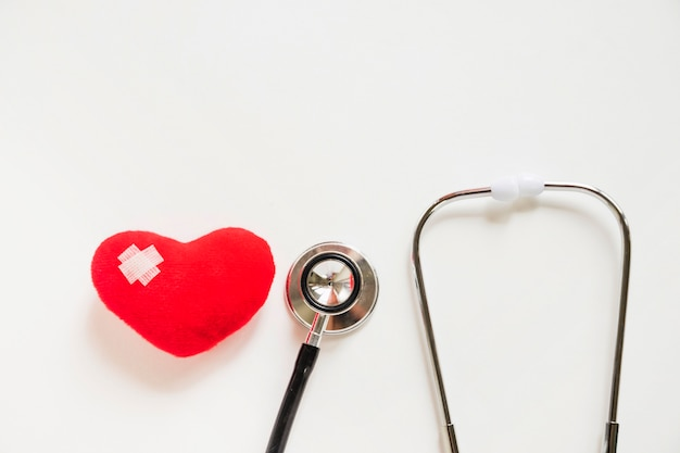 Red heart with bandages and stethoscope on white background