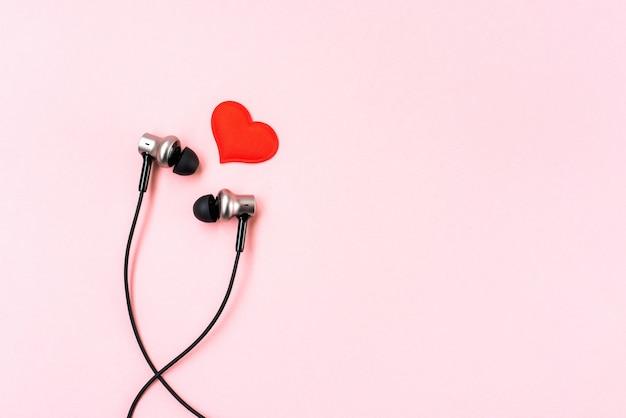 Красное сердце с черными музыкальными наушниками на розовой пастели