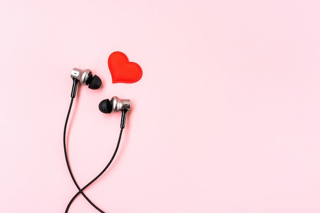 Red heart with black music earphones on pink pastel